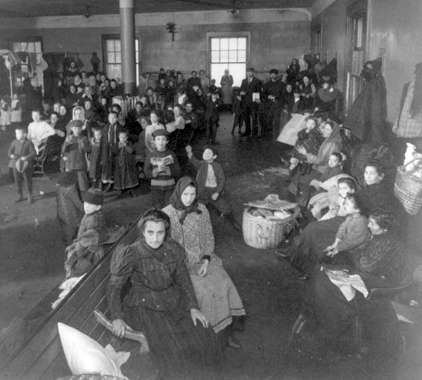 Newly arrived immigrants in waiting room at Ellis Island, New York, 1907 (Library of Congress)
