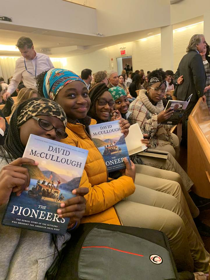 Students from Brooklyn East Collegiate display their copies of David McCullough's latest book at the Trinity School.