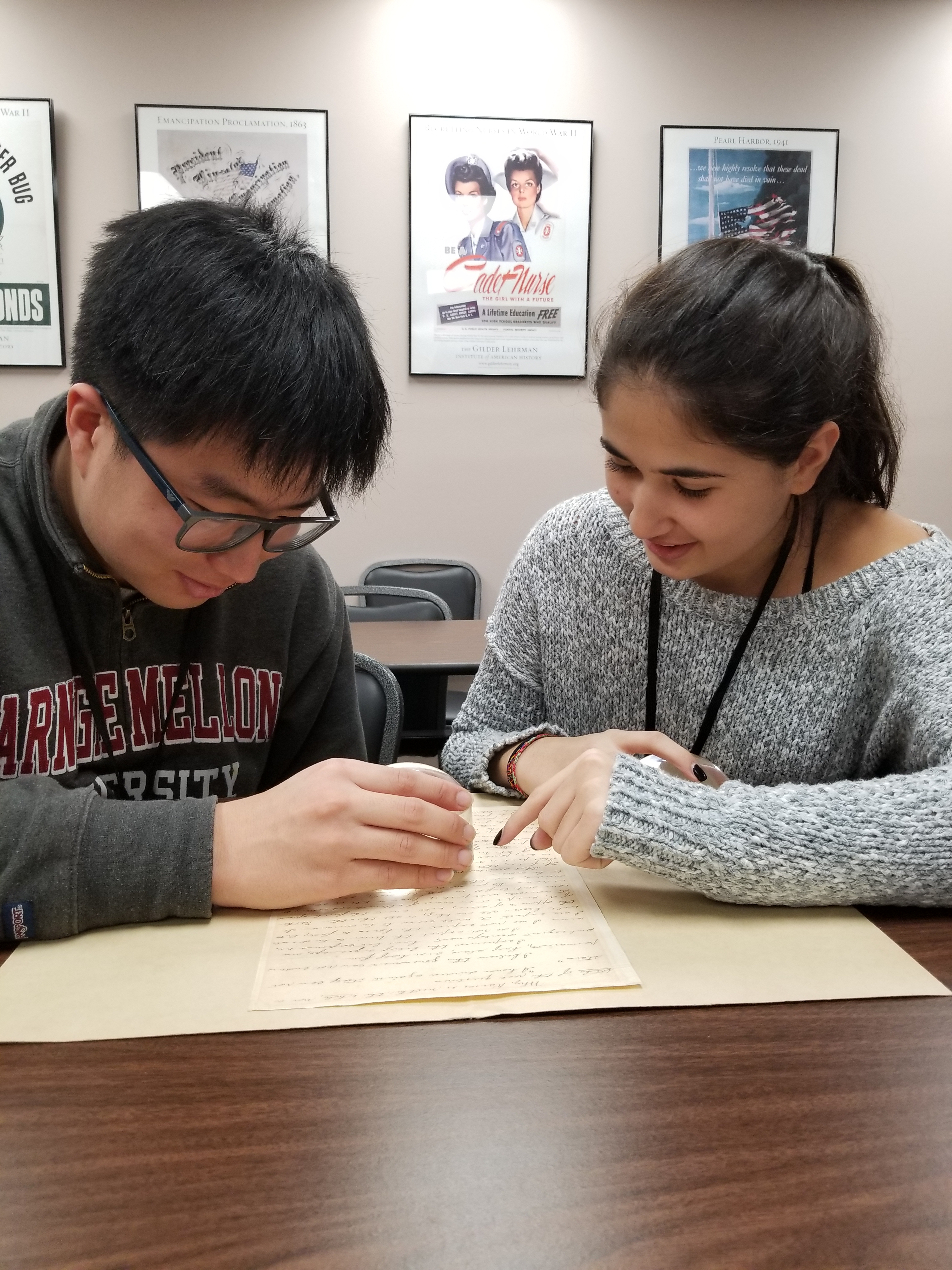 Student interns Jae Joon Lee and Zoubida Bicane examine a document from the Collection.