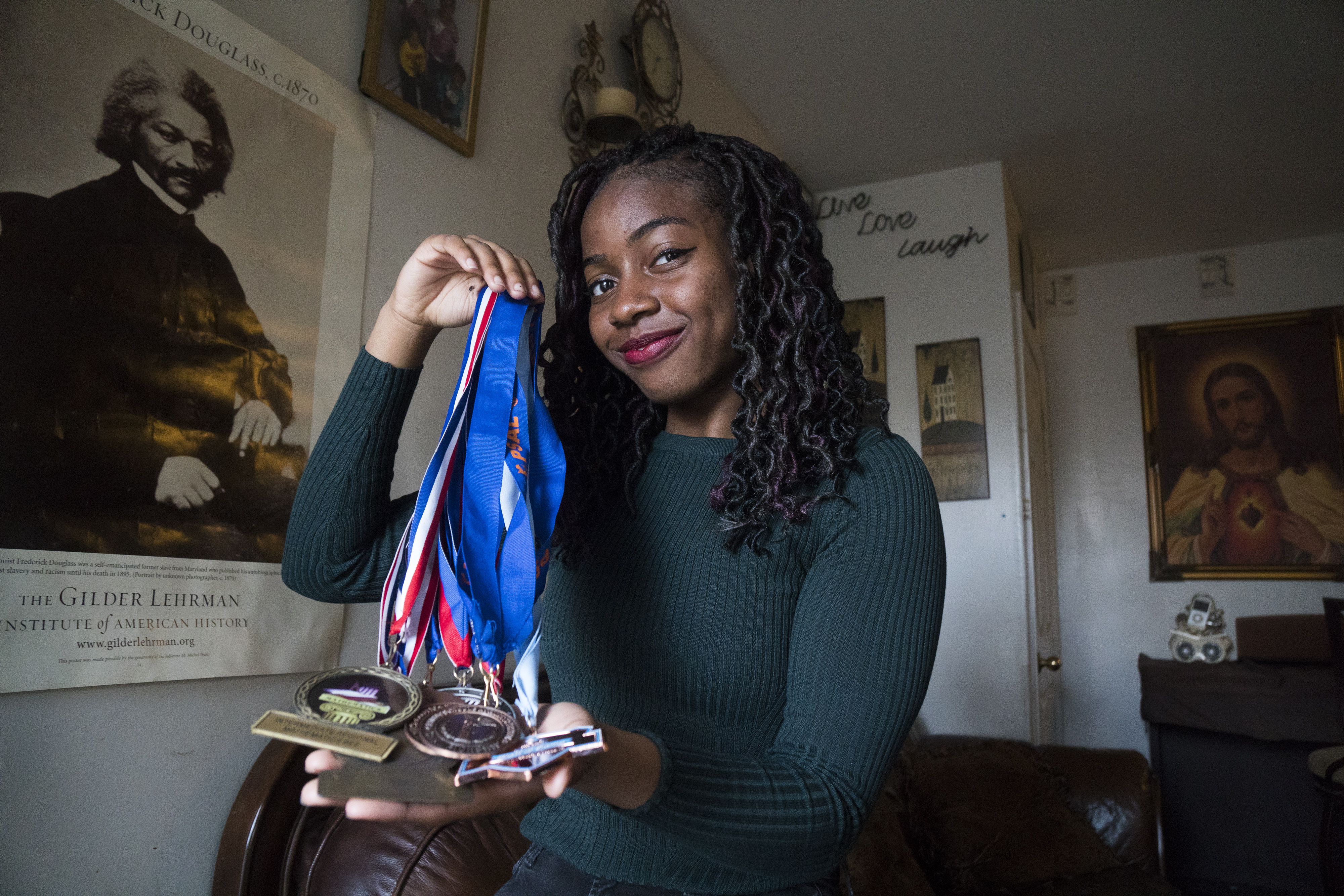 Venus Nnadi holding up medals in her Queens home (Go Nakamura/New York Daily News)