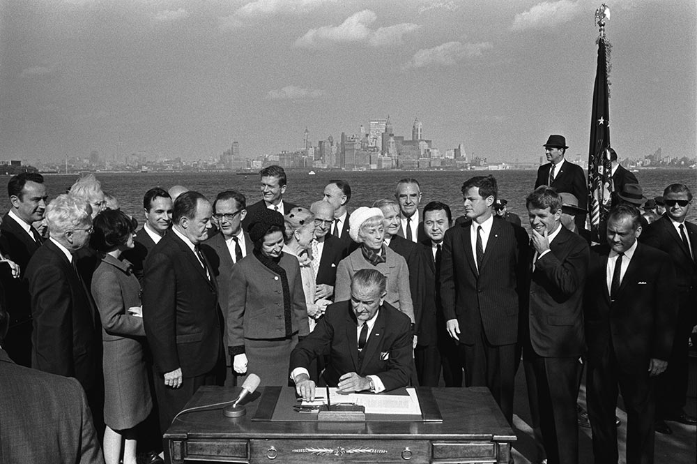 President Lyndon B. Johnson signs the Immigration Act as Vice President Hubert Humphrey, Lady Bird Johnson, Muriel Humphrey, Sen. Edward Kennedy, Sen. Robert F. Kennedy, and others look on, photograph by Yoichi Okamoto, October 3, 1965 (White House Photo Office / Lyndon Baines Johnson Presidential Library)