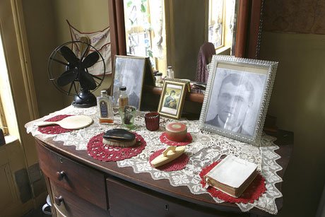 Period dresser in the restored Baldizzi apartment with photographs of Adolpho Ba
