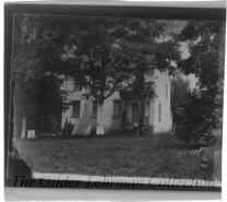 Miller's House [Sharpsburg, MD.], on Antietam battlefield, with family standing on porch.